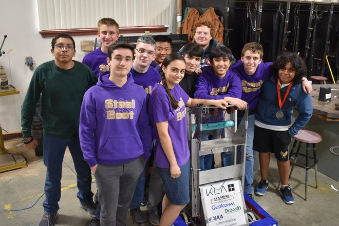 """Most of the Salinas High School Robotics Team shown posing for a photo alongside their robot, """"Steel Boot."""""""