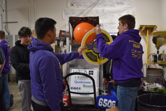 "Mateo Brambila, Thomas An and Michael Montemurno set up a hatch next to their ""Steel Boot"" robot at Salinas High School."