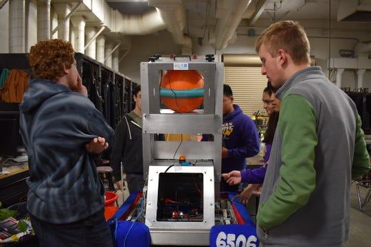 "The Salinas High School Robotics Team discussing their ""Steel Boot"" robot."
