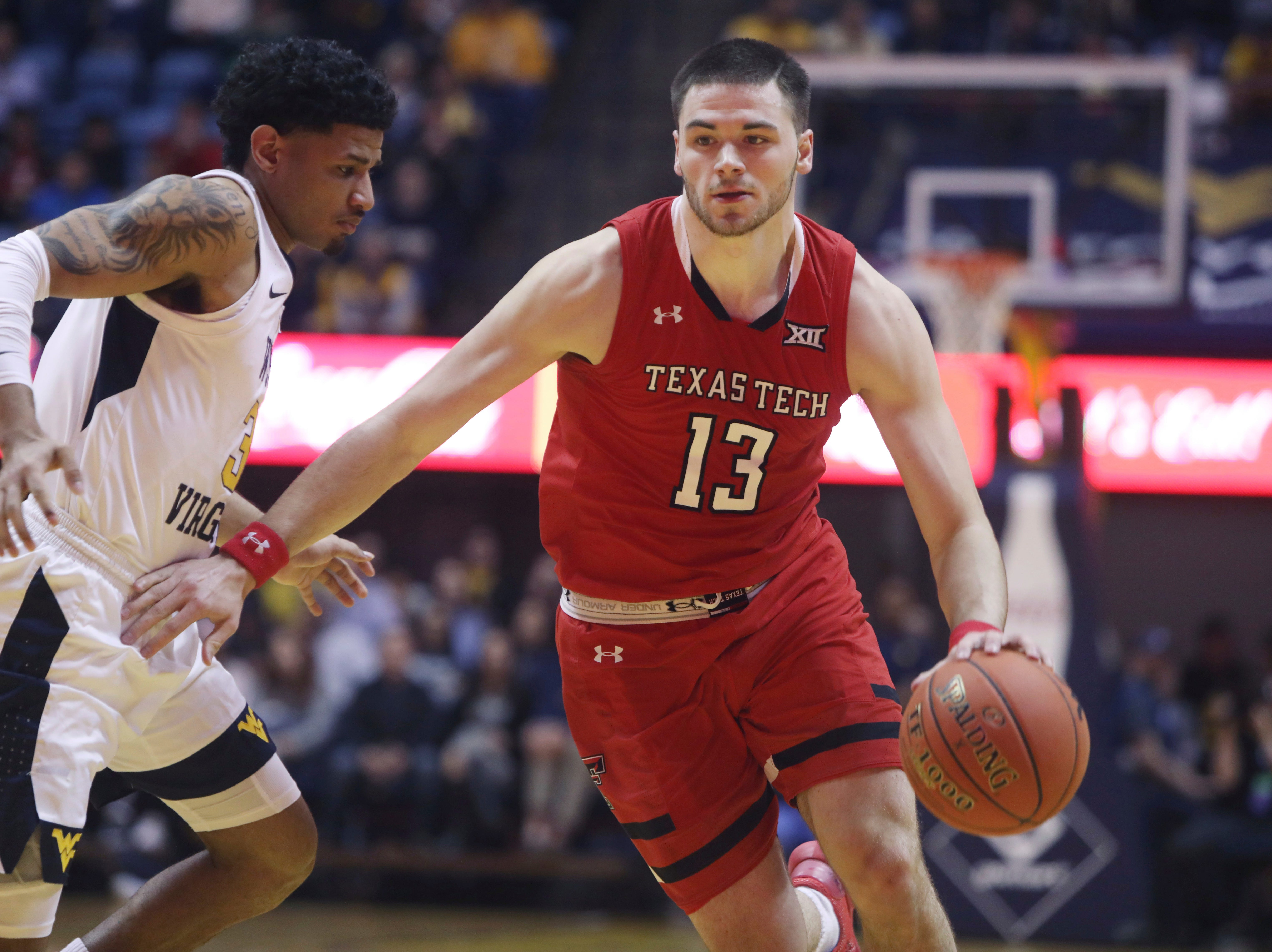 Texas Tech guard Matt Mooney (13) drives up court while defended by West Virginia guard James Bolden (3) during the first half of an NCAA college basketball game Wednesday, Jan. 2, 2019, in Morgantown, W.Va.