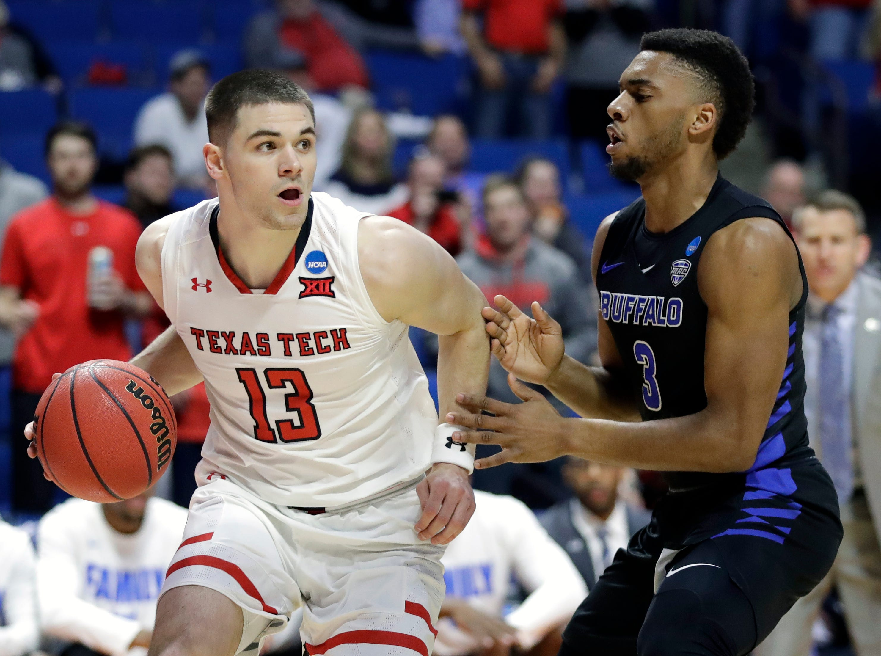 Texas Tech's Matt Mooney (13) drives around Buffalo's Jayvon Graves during the first half of a second round men's college basketball game in the NCAA Tournament Sunday, March 24, 2019, in Tulsa, Okla. (AP Photo/Jeff Roberson)