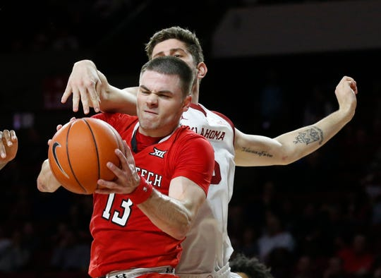 Texas Tech guard Matt Mooney (13) grabs a rebound in front of Oklahoma forward Matt Freeman, right, in the second half of an NCAA college basketball game in Norman, Okla., Saturday, Feb. 9, 2019. (AP Photo/Sue Ogrocki)
