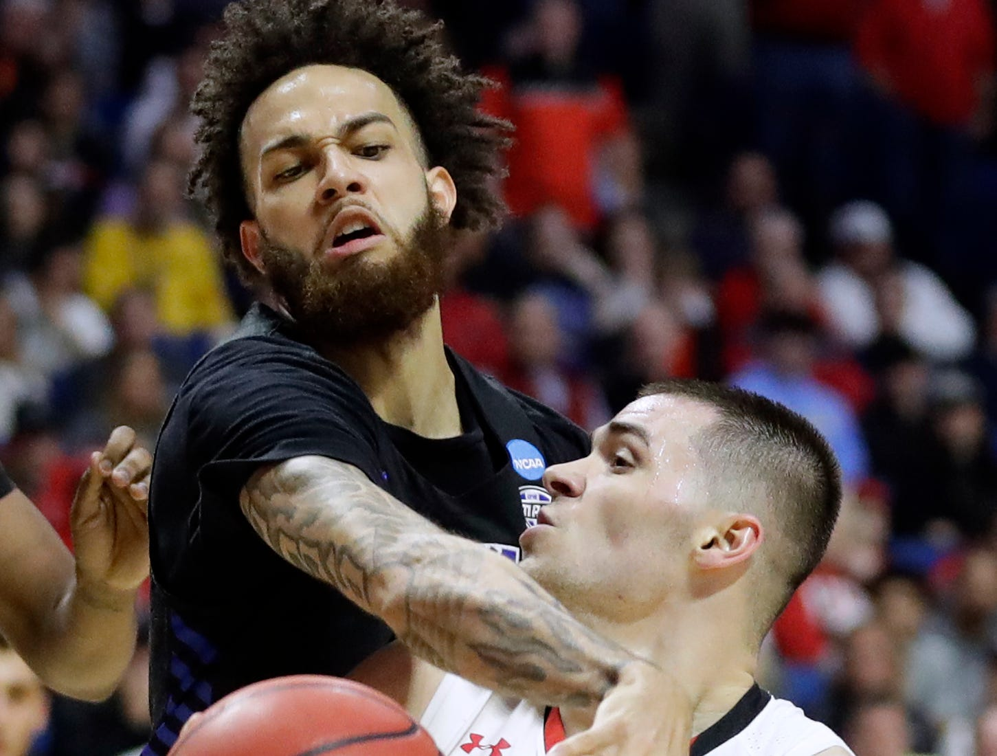 Texas Tech's Matt Mooney, bottom, looks to the basket as Buffalo's Jeremy Harris defends during the first half of a second round men's college basketball game in the NCAA Tournament Sunday, March 24, 2019, in Tulsa, Okla. (AP Photo/Jeff Roberson)