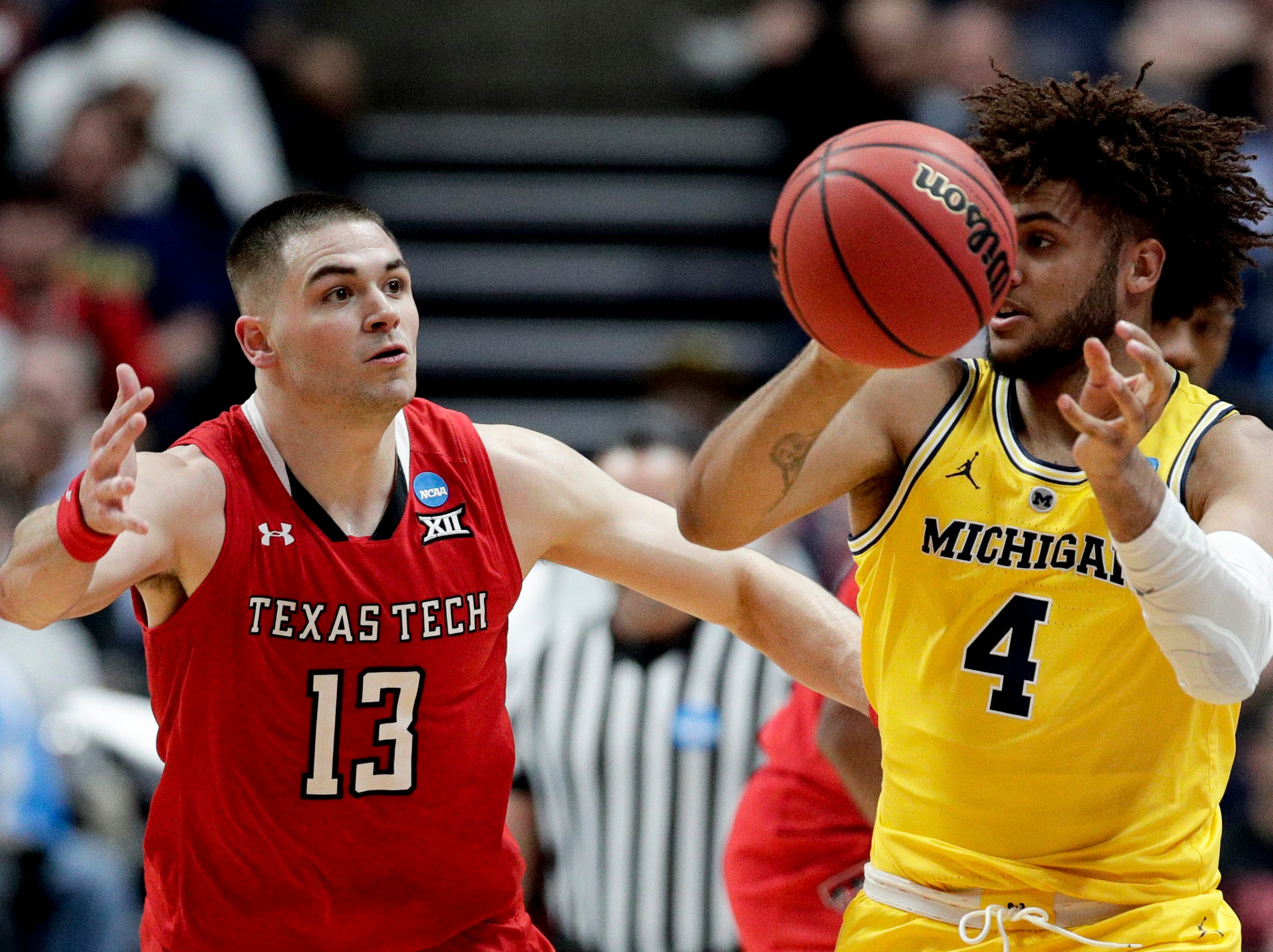 Michigan forward Isaiah Livers, right, passes the ball around Texas Tech guard Matt Mooney during the first half an NCAA men's college basketball tournament West Region semifinal Thursday, March 28, 2019, in Anaheim, Calif. (AP Photo/Jae C. Hong)