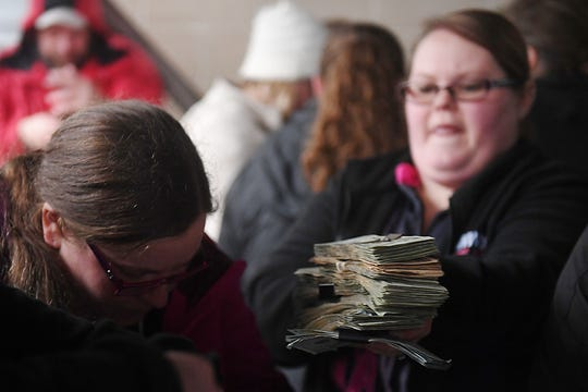 Stacks of money is handed to Sara Pearson, president of the Pink Ladies, for the more than $200K raffle Wednesday, April 3, in Hudson.