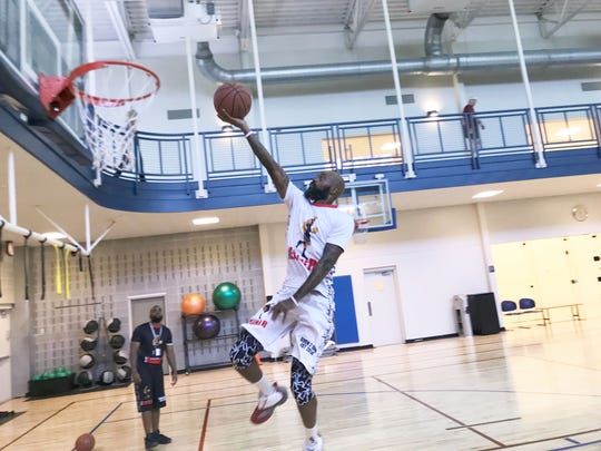 Dominique Farmer drives to the basket with a finger roll at Premier Health & Fitness Center in Tallahassee.
