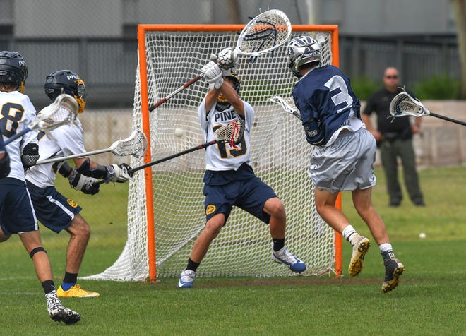 Drew Sternberg (right) of St. Edward's School, of Vero Beach, fires a shot past RJ Lichten (center) to score against The Pine School in the 3rd period of boy's varsity lacrosse on Thursday April 4, 2019,at The Pine School in Hobe Sound. St Edward's School won 17-3.  Drew Sternberg, RJ Lichten