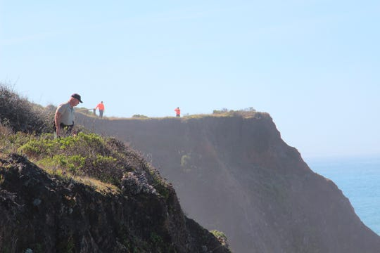 In this March 29, 2018, file photo, Deputy Bill Holcomb looks down the cliff near the crash site near Mendocino as volunteers scour the area behind him on and resume looking for children, still missing after their parent's SUV plunged into the ocean.