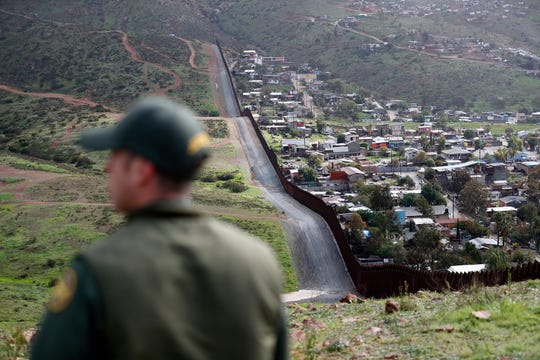 In this Feb. 5 photo, Border Patrol agent Vincent Pirro looks on near a border wall that separates the cities of Tijuana, Mexico, and San Diego.
