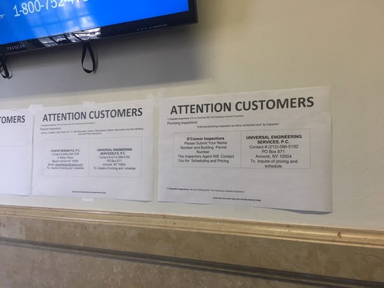 Signs outside Mount Vernon Department of Buildings detailing which outside firms are available for plumbing and other inspections