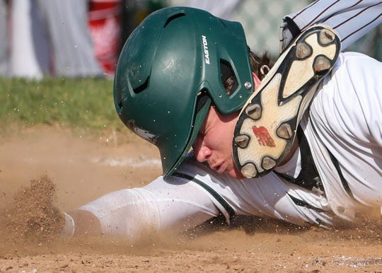St. Mark's Nick Pisorchik is safe at home with the Spartans' first run of the game as he slides in under the tag (and foot) of Appoquinimink pitcher Mason Keene on a pitch to the backstop in the third inning of the Jaguars' 5-2 win at St. Mark's High School Thursday.