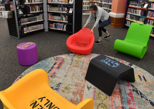 Wichita Falls Public Library administrator Jana Hausburg moves some of the furniture in the teens section of the library. The library wants to replace heavy oak chairs with more kid-friendly furniture in the childrens section.