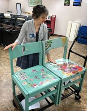 Jana Hausburg, library administrator, talks about two of the art chairs created for the upcoming Chair-ity Art Auction event to raise money for new chairs in the childrens section of the Wichita Falls Public Library.