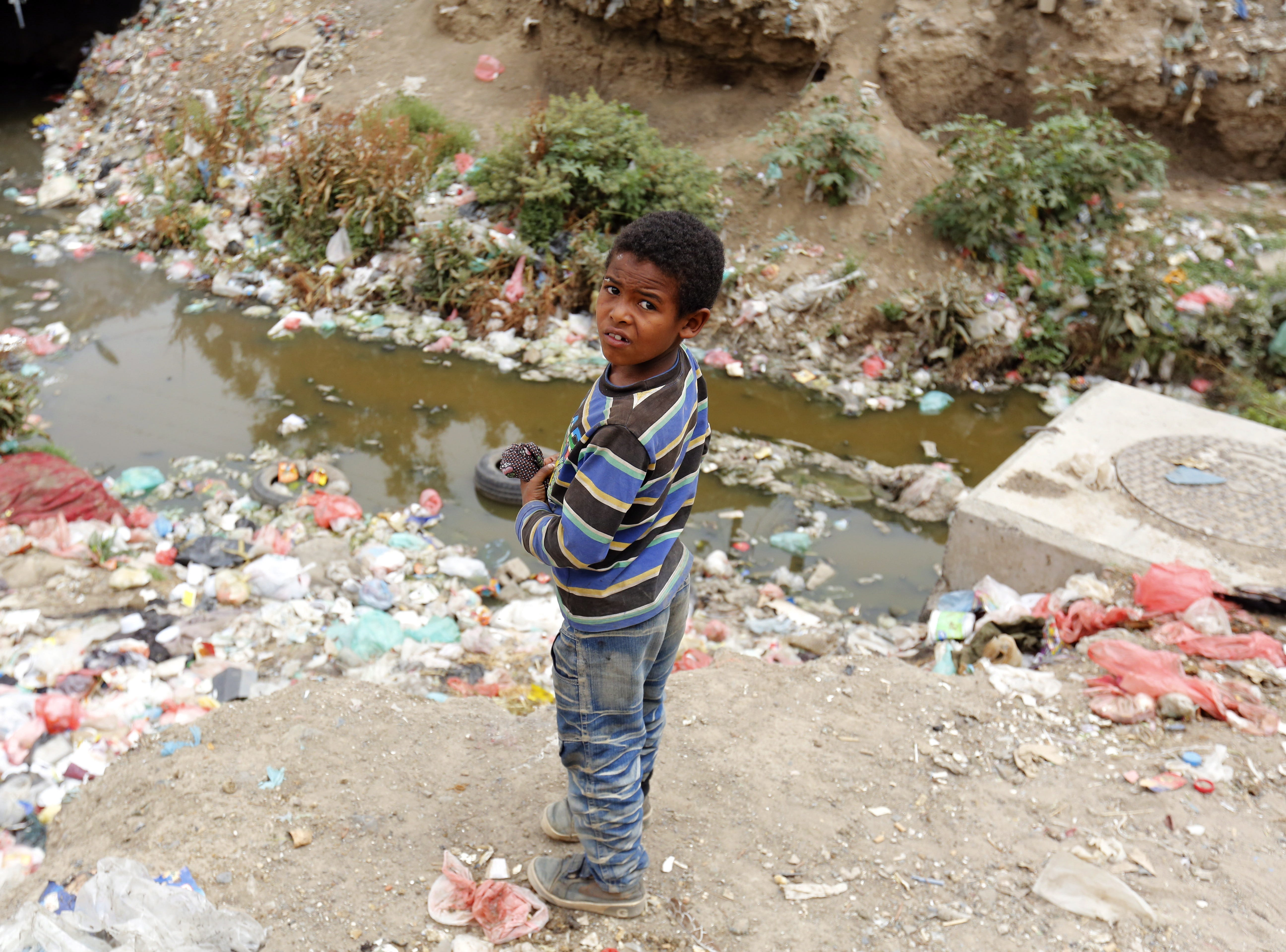 A Yemeni child stands near a sewage swamp covered with waste at a neighborhood, creating a high-risk environment for cholera, amid a rapidly spreading cholera outbreak, in Sana'a, Yemen on April 1, 2019. According to reports, a new wave of a rapidly spreading cholera outbreak in Yemen is getting worse with 10 thousand new cases reported every week since the beginning of 2019, affecting almost 110 thousand people and killing over 200 people.