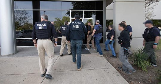 ICE agents enter a business in Allen, Texas, on April 3, 2019.