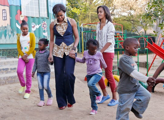 Sasha, Michelle and Malia Obama play with children while visiting a community center in Johannesburg, South Africa on June 21, 2011.