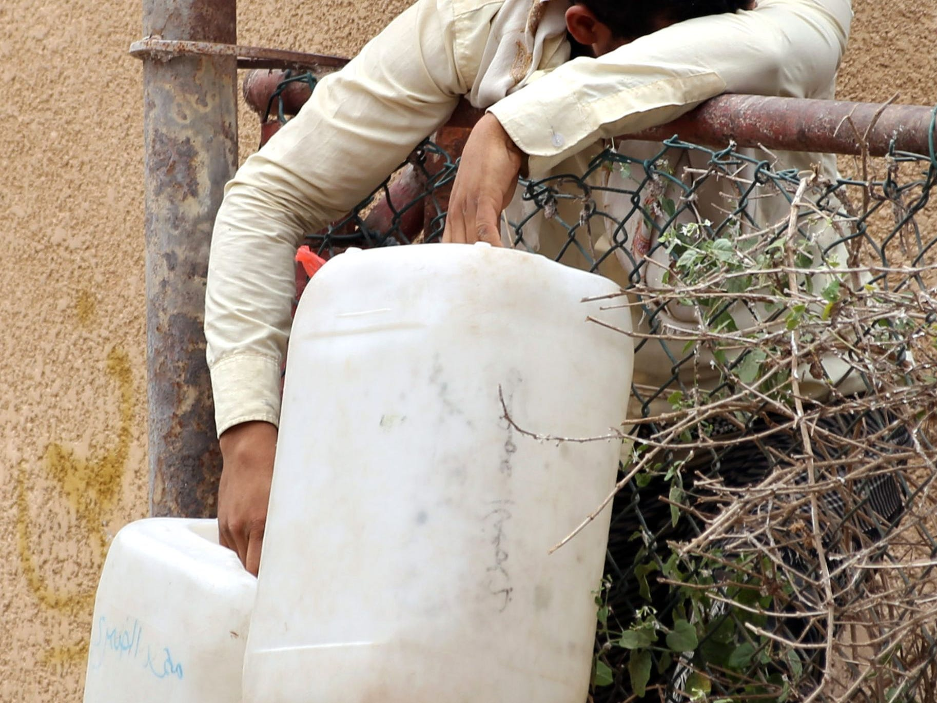 A Yemeni man holds plastic containers as he waits to collect water from a tank in the southwestern Yemeni city of Taez, on April 3, 2019. The war in Yemen has left thousands dead and triggered the world's worst humanitarian crisis, according to the United Nations. According to Action Contre la Faim 16 million people lack access to water and sanitation and basic health care. Fifty percent of Yemen's clinics are closed and more than 70 percent do not have a regular supply of medicine.