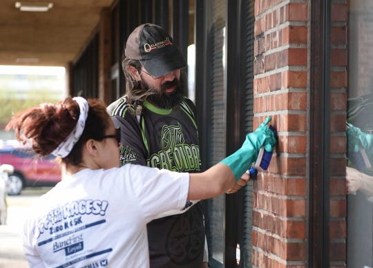 Volunteers Emily Nicholls and Andy Jacobs use brushes to clean the wall outside the Democratic Party office in Norman, Okla., where racist, anti-gay and anti-Semitic graffiti were found on Wednesday, April 3, 2019.