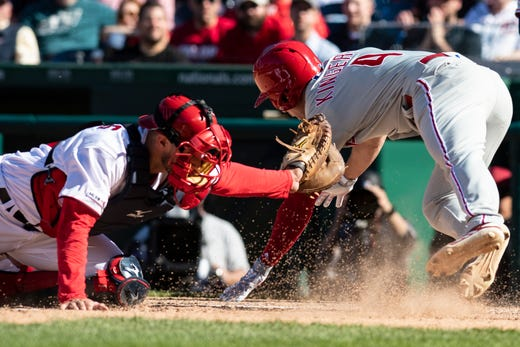 April 3: Philadelphia's Scott Kingery avoids a tag by Nationals catcher Yan Gomes.