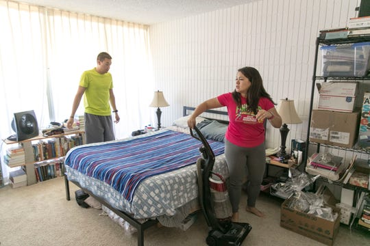 Honolulu teacher Jennifer Howe and her husband, Cyrus Howe, tidy up their bedroom. The Howes pay $1,625 a month in rent for roughly 600 square feet in a quiet neighborhood just ten minutes' walking distance from Jennifer Howe's work.