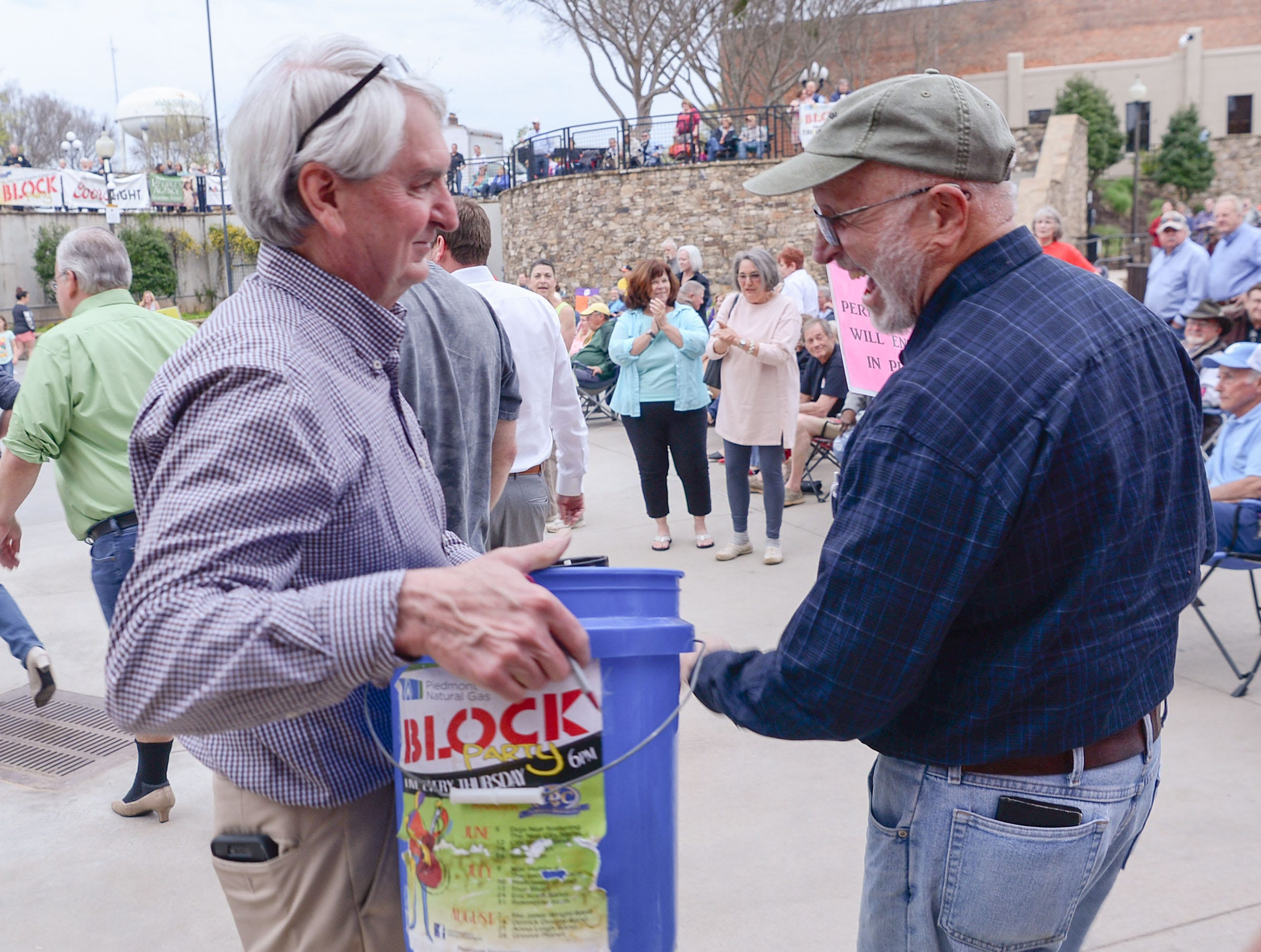 Carey Jones, Jr., left, brings a donation bucket by Bill West of Anderson, during a break when Combo Kings played music during the Main Street Program Block Party at Carolina Wren Park in downtown Anderson Thursday.