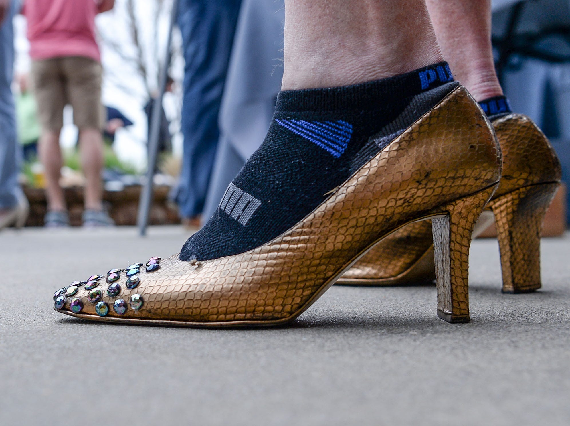 """Foothills Alliance held the """"Walk a Mile in Her Shoes"""" event to bring awareness to National Sexual Assault Awareness Month, during a break in the Main Street Program Block Party music by Combo Kings at Carolina Wren Park in downtown Anderson Thursday."""