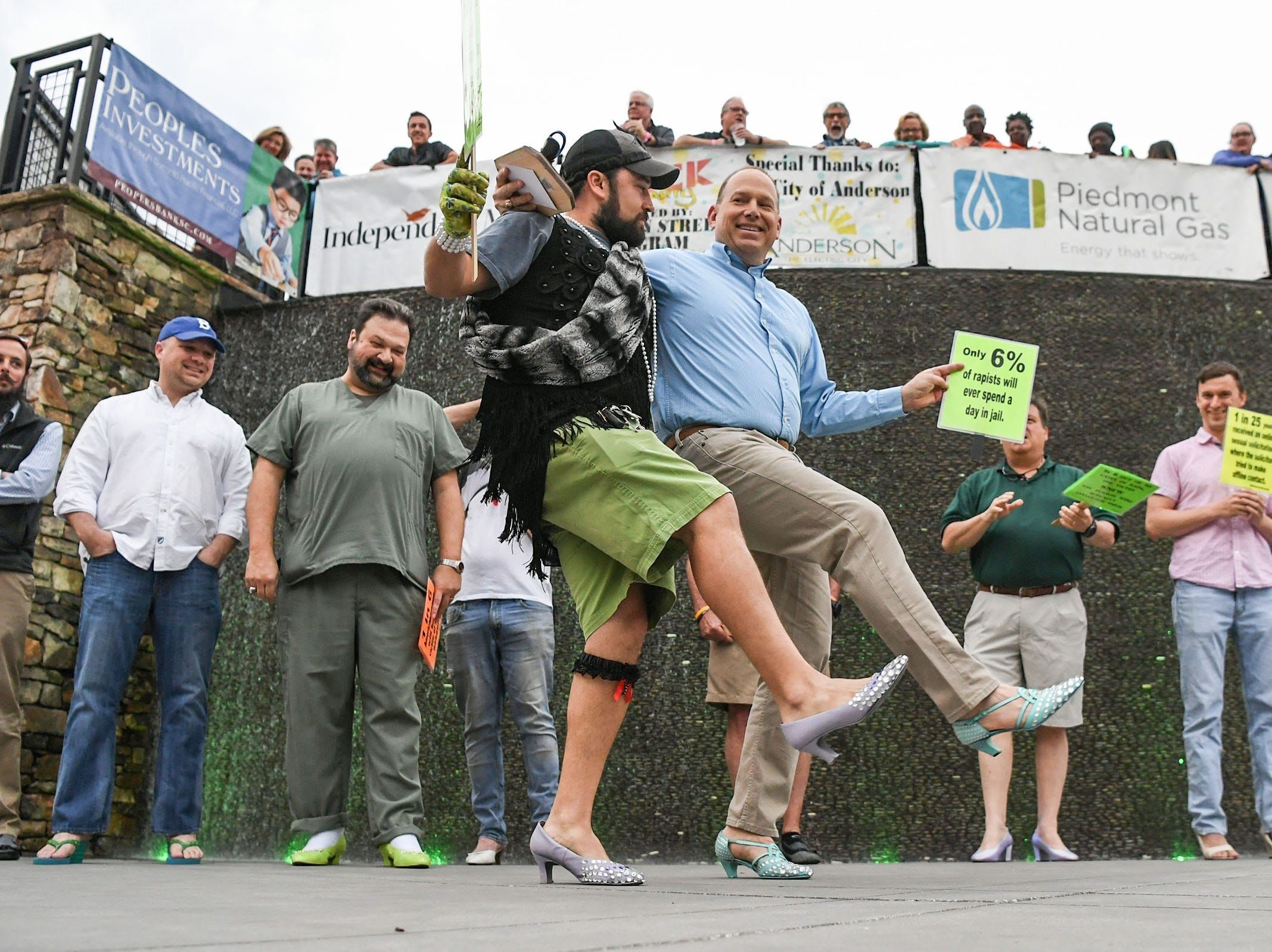 """David Thornton, left, and Virgil Hobbs, right, show a little dance with high heels during Foothills Alliance """"Walk a Mile in Her Shoes"""" event at Carolina Wren Park in downtown Anderson Thursday. The walk is held each year to bring awareness to National Sexual Assault Awareness Month during a break in the Main Street Program Block Party."""