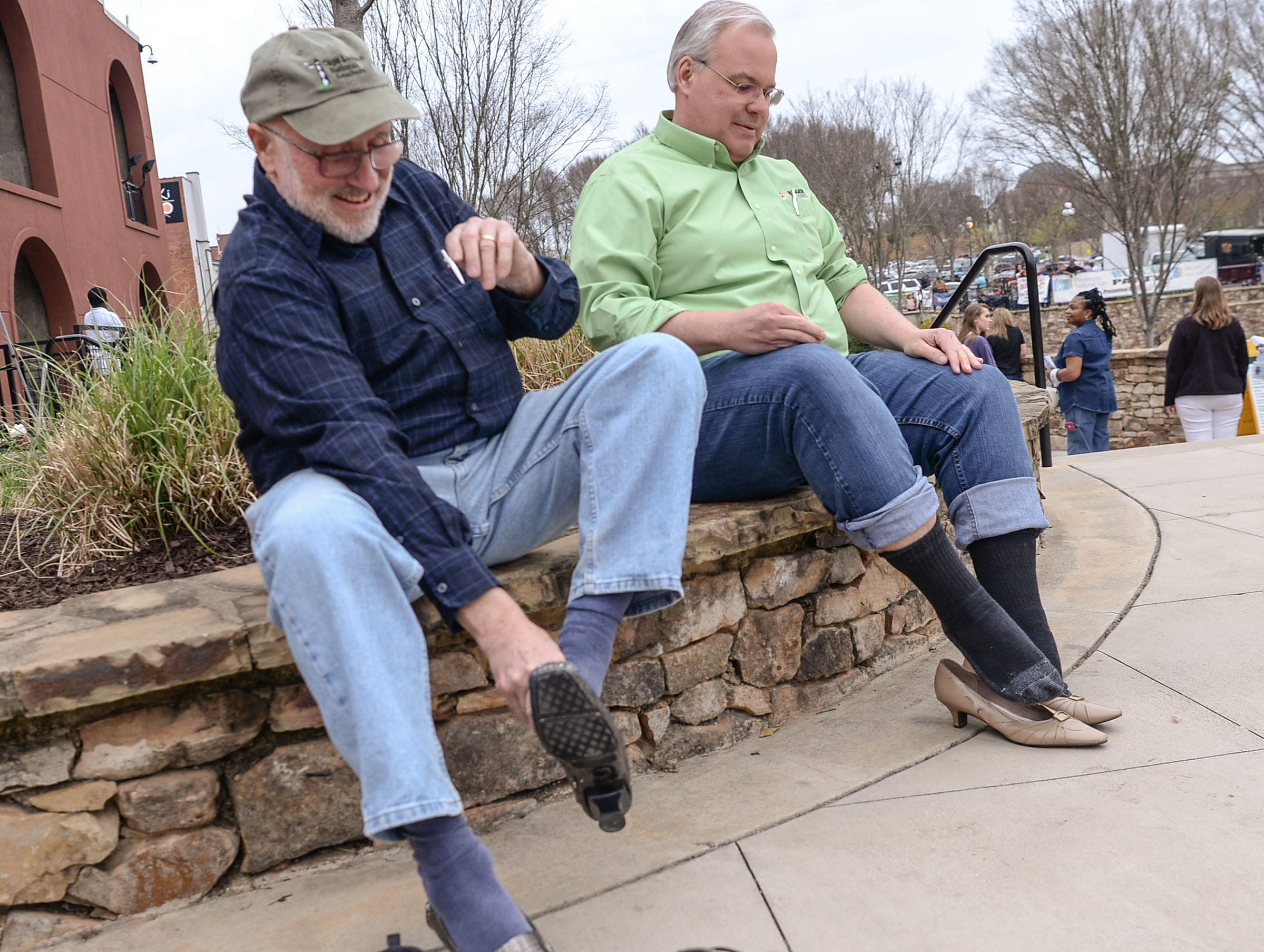 """Bill West, left, and Chip Reaves, right, both representing St. John's United Methodist Church, put on high-heels before the Foothills Alliance """"Walk a Mile in Her Shoes"""" event to bring awareness to National Sexual Assault Awareness Month, during a break in the Main Street Program Block Party music by Combo Kings at Carolina Wren Park in downtown Anderson Thursday."""