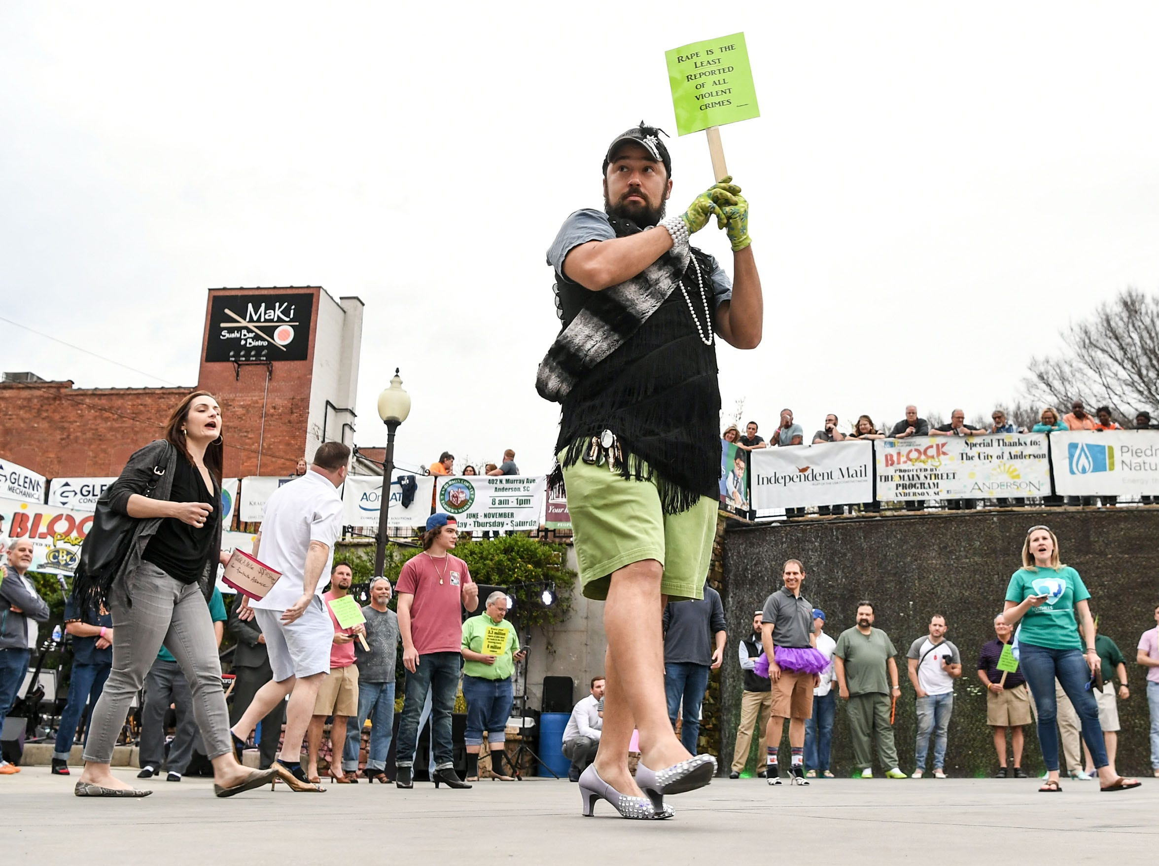 """David Thornton of Anderson holds a sign up and wears high-heels for the Foothills Alliance """"Walk a Mile in Her Shoes"""" event, to bring awareness to National Sexual Assault Awareness Month during a break in the Main Street Program Block Party at Carolina Wren Park in downtown Anderson Thursday."""
