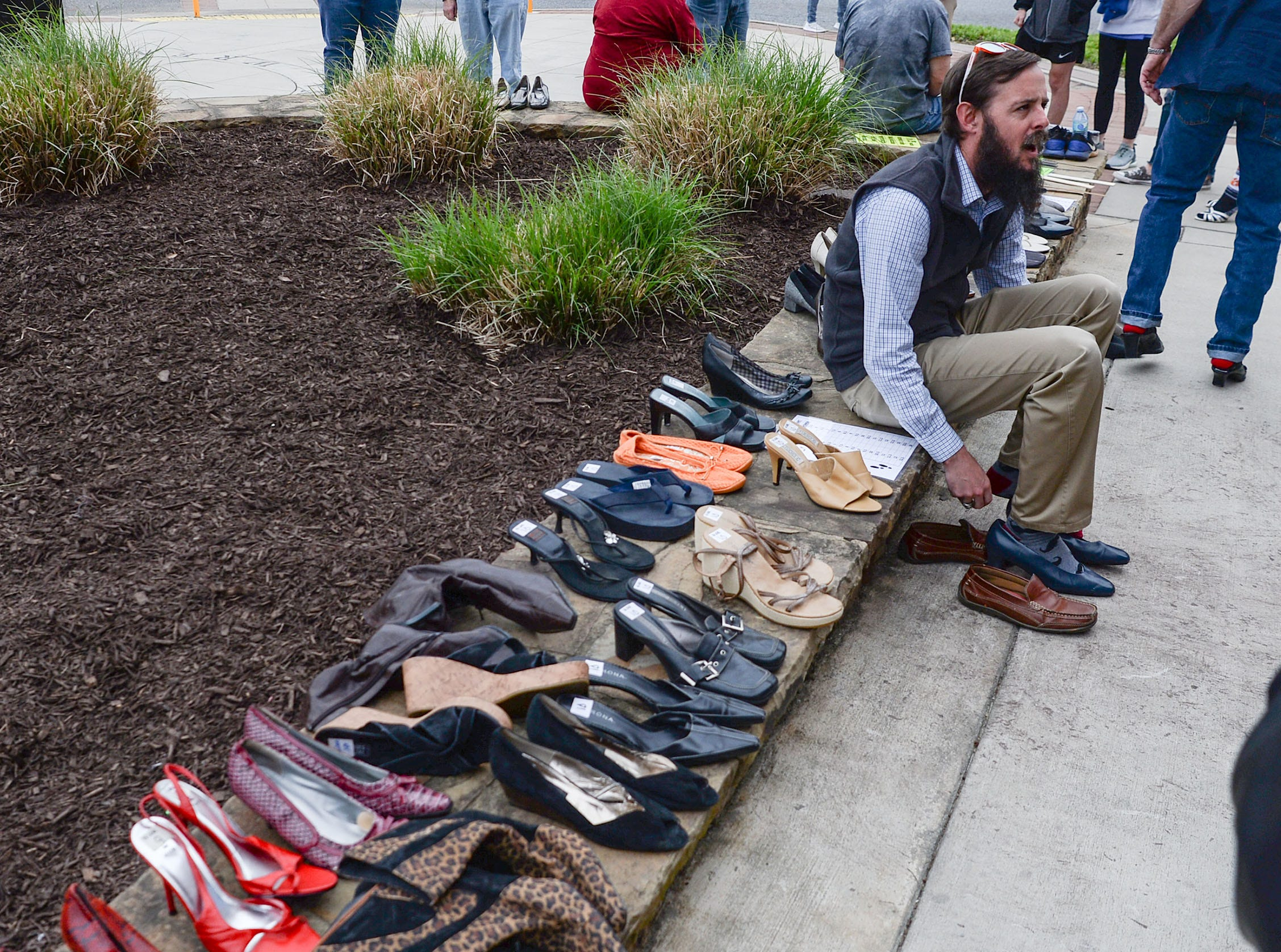 """Blake Sanders, West Pelzer mayor, puts on high-heels before the Foothills Alliance """"Walk a Mile in Her Shoes"""" event to bring awareness to National Sexual Assault Awareness Month, during a break in the Main Street Program Block Party music by Combo Kings at Carolina Wren Park in downtown Anderson Thursday."""