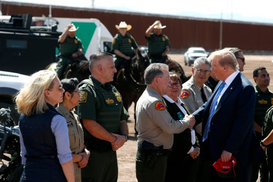 President Donald Trump visits a new section of the border wall with Mexico in Calexico, Calif., Friday April 5, 2019. at left is Homeland Security Secretary Kirstjen Nielsen.