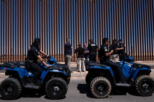 Mexico's federal police and US security agents meet near the US-Mexico border fence as seen from Mexicali, Baja California state, Mexico, on April 5, 2019, within the security operation prior to the visit of President Donald Trump to the border city of Calexico, in California.
