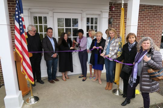 Porch gather on the porch for the ribbon-cutting for the new Family Promise emergency shelter on the old Fort Monmouth property in Oceanport Friday, April 5, 2019.