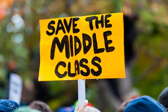 """A protest sign reading """"Save the Middle Class""""."""