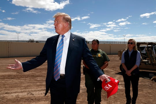 President Donald Trump visits a new section of the border wall with Mexico in Calexico, Calif., Friday April 5, 2019. Gloria Chavez with the U.S. Border Patrol, center, and Homeland Security Secretary Kirstjen Nielsen listen.