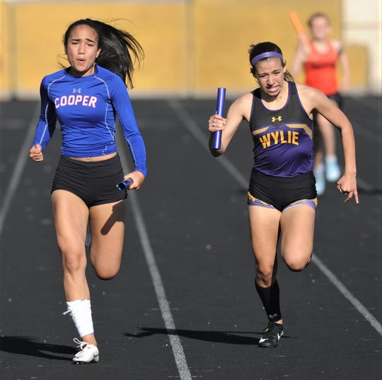 Cooper's Lexa Garcia, left, races Wylie's Leandra Benton to the finish line the 800-meter relay. Cooper won the race in 1:46.06, while Wylie was second (1:46.28) at the District 4-5A track and field meet Thursday, April 4, 2019, at Aledo's Bearcat Stadium.