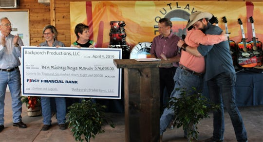 Kerry Fortune, program president of Ben Richey Boys Ranch, hugs Outlaws & Legends Music Festival founder and organizer Mark Powell after Powell announced a gift of $76,698 to the organization from 2019 show proceeds.