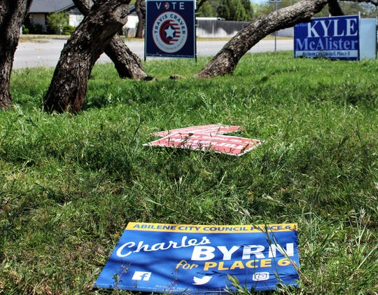Yard signs for Abilene City Council candidates Charles Byrn and David Turvaville were moved for mowing near Abilene Woman's Club but larger signs reinforced with rebar for Kyle McAlsiter and Travis Craver stand tall.