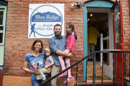 Jennifer Pharr Davis, left, holds her son, Gus, as she stands on the steps of her new store, Blue Ridge Hiking Company, with her husband, Brew Davis, and daughter, Charley in downtown Asheville April 5, 2019.