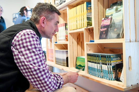 N.C. State Rep. Brian Turner looks at a display of maps during the grand opening of Jennifer Pharr Davis' new store, Blue Ridge Hiking Company, in downtown Asheville April 5, 2019.