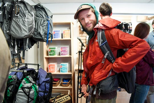 Vaughan Jensen adjusts the straps of a backpack as he tries it on during the grand opening of Jennifer Pharr Davis' new store, Blue Ridge Hiking Company, in downtown Asheville April 5, 2019. Jenson, who plans to hike the Pacific Crest Trail next year, liked the fact that the store offered products from smaller companies.