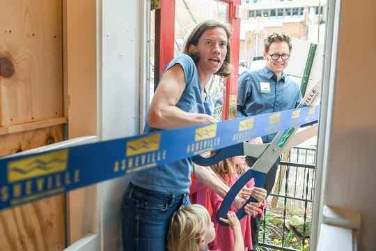 Jennifer Pharr Davis cuts a ribbon during the grand opening celebration of her new store, Blue Ridge Hiking Company, in downtown Asheville April 5, 2019.