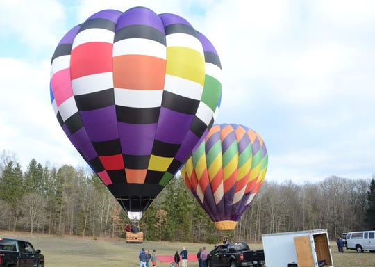 Tyler Jaques leaves the ground in his new balloon, left, while Pat Rolfe follows.