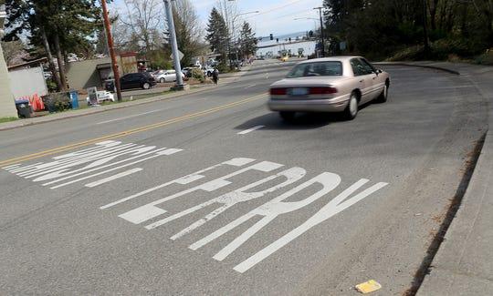 A car heads down the ferry lane of Bainbridge Island's Olympic Drive on Thursday.