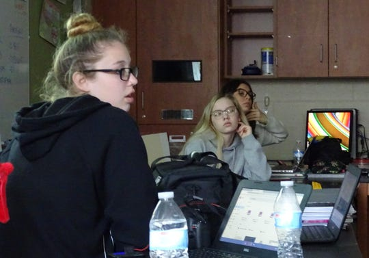 Kelly Stratton, Kylee Tighe and Makenzie Tighe listen to critiques during a photo editing session on Tuesday at Bucyrus High School.