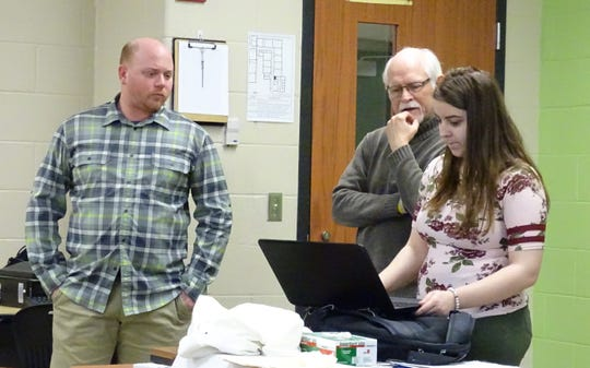 Artist in Residence Gary Harwood helps Bucyrus High School senior Alexis Pival edit some if her recent photos at the school Tuesday morning as art teacher Mike Striker, left, watches.