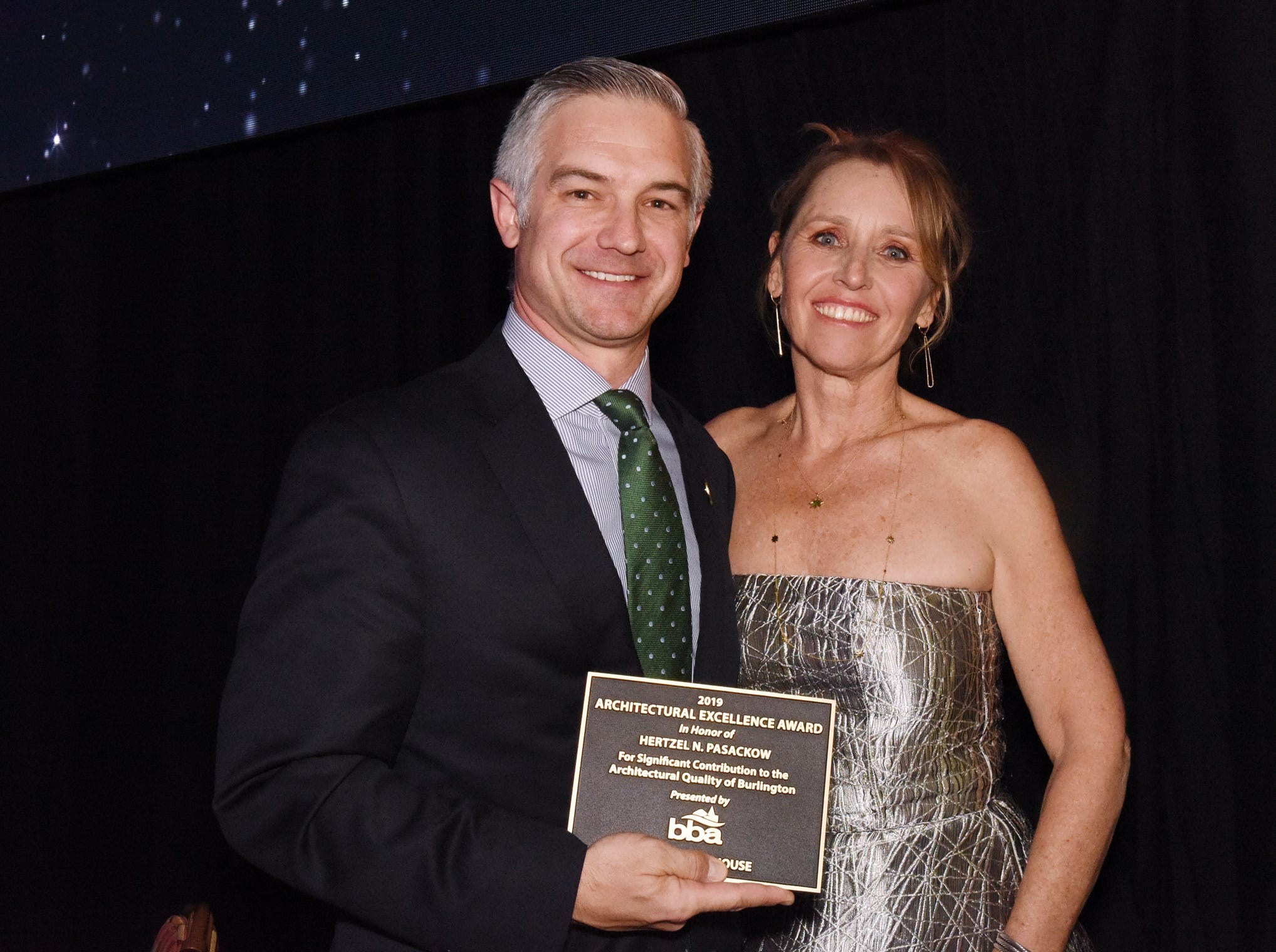 Shane Jacobson, president and CEO of the University of Vermont Foundation, accepts the 2019 Architectural Excellence Award in honor of Hertzel N. Pasackow, from Kelly Devine, executive director of the BBA, at the 41st BBA Burlington Business Association Dinner & Annual Meeting at the Hilton Burlington Lake Champlain in Burlington, VT on Thursday, April 4, 2019.