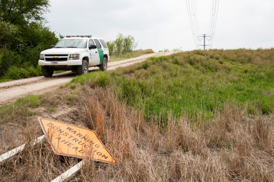 "A Border Patrol vehicle drives down an embankment near a sign that reads ""Warning Construction Ahead"" along a levee in Hidalgo County, Texas on Friday, April, 5, 2019. Construction of 13 miles of border fence is scheduled to start in Hidalgo County, Texas."