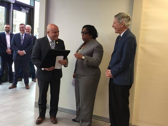 Michele Lawrence, Chase Bank's regional director for Pennsylvania, Delaware and South Jersey, accepts a proclamation from Camden Mayor Frank Moran as Subaru of America CEO Thomas Doll looks on.