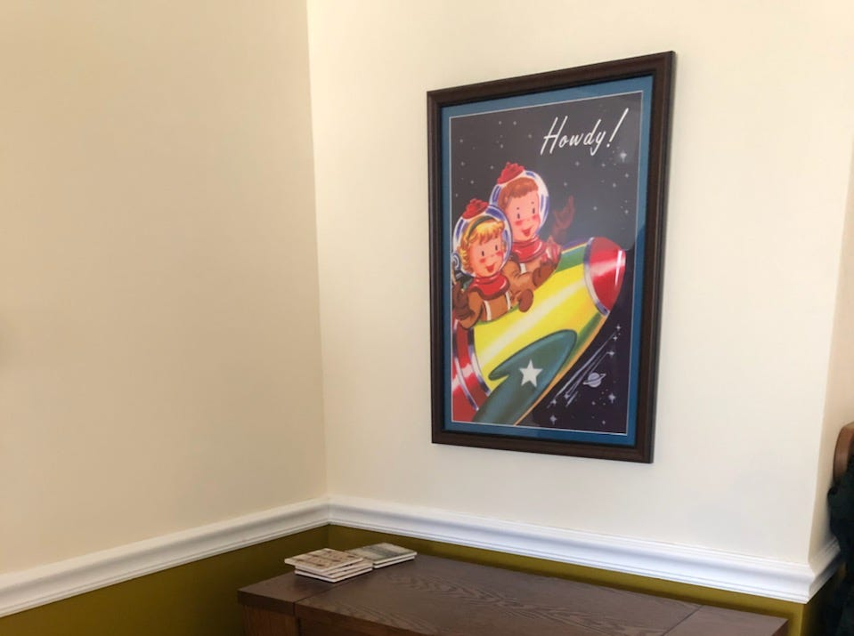 A retro poster and wine cabinet add retro style to the Chapmans' Cherry Hill home. Jonathan Chapman mixes cocktails inspired by classic movies.